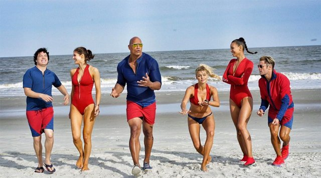 Baywatch Cast Photo Shows A Rock on a Beach With Some Babes